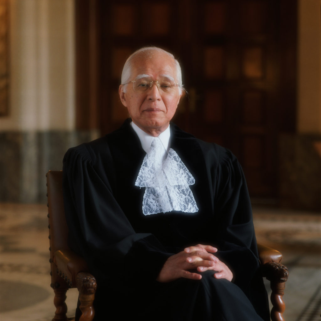 Judge Hisashi Owada is pictured sitting in a chair, wearing his formal robes.